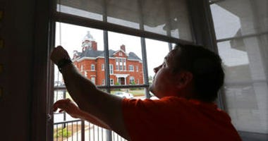 Brian Lambert, owner of Scoops, a coffee and sweets shop, opens up the windows of his business across the street from the Forsyth Courthouse as he gets ready to reopen next week in Forsyth, Ga. (Curtis Compton/tlanta Journal-Constitution via AP)