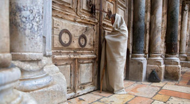 A Christian worshiper stands at the closed door of the Church of the Holy Sepulchre, believed by many Christians to be the site of the crucifixion and burial of Jesus Christ, in Jerusalem, Friday, April 10, 2020. (AP Photo/Sebastian Scheiner)