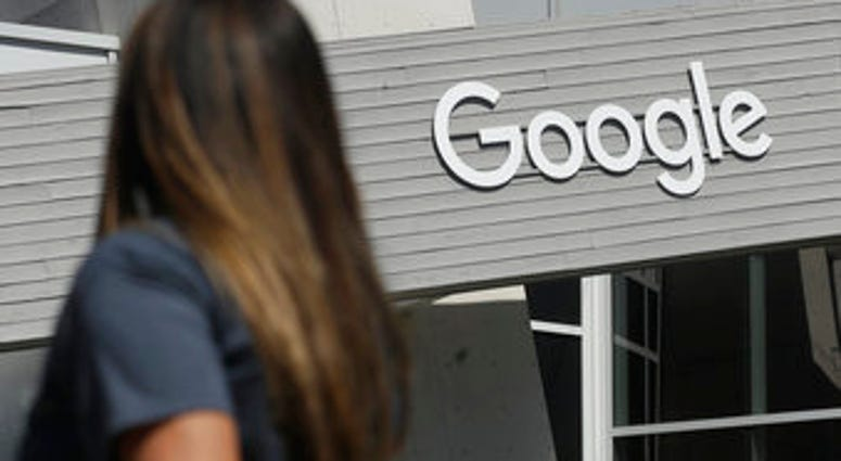 FILE - In this Sept. 24, 2019, file photo, a woman walks below a Google sign on the campus in Mountain View, Calif. New Mexico is suing Google over allegations that the tech company is illegally collecting personal data. (AP Photo/Jeff Chiu, File)