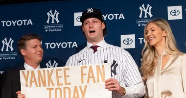 New York Yankees pitcher Gerrit Cole, center, holds a sign he used as a young Yankees fan, as he is introduced as the baseball clubs newest player during a baseball media availability, Wednesday, Dec. 18, 2019 in New York. (AP Photo/Mark Lennihan)