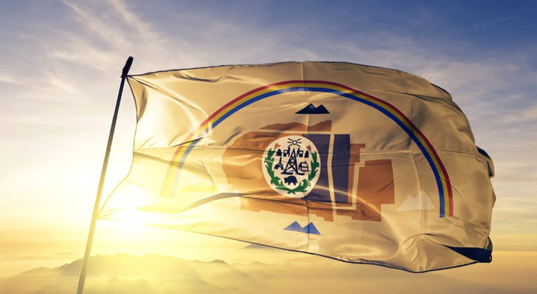 Navajo flag textile cloth fabric waving on the top sunrise mist fog