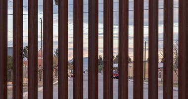 Looking at the border fence between the USA and Mexico, with a town in Mexico visible on the other side