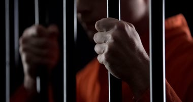 criminal holding jail bars feeling regret for committing crime closeup