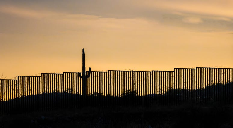 US -Mexico border wall at sunset with iconic saguaro cactus - stock photo