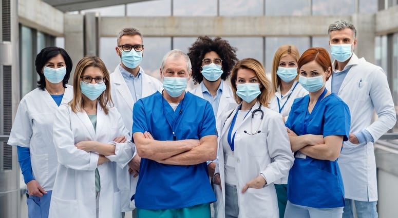 A group of doctors with face masks looking at camera,