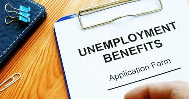 Man fills in Unemployment benefits application form.