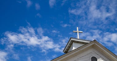 Church Steeple And Cross Set Against A Blue Sky