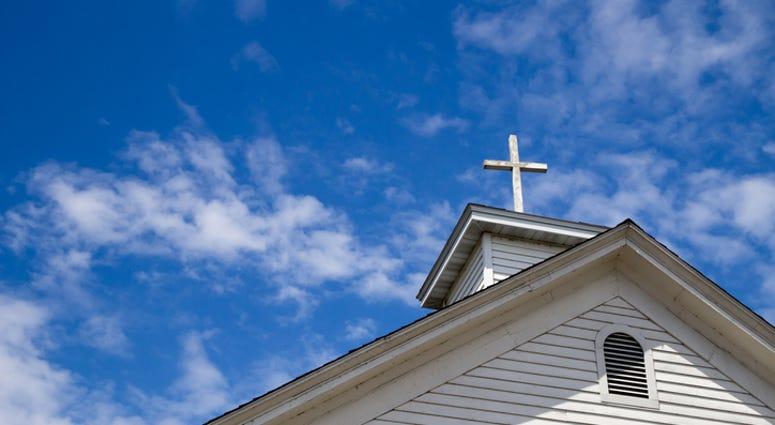 Church Steeple And Cross Set Against A Blue Sky