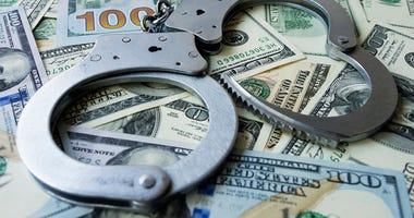 Handcuffs on a pile of US dollar banknotes- symbolic image of a bribe, laundering of money or corruption.