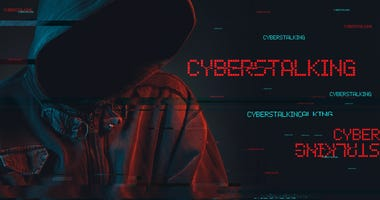 Cyberstalking concept with faceless hooded male person, low key red and blue lit image and digital glitch effect