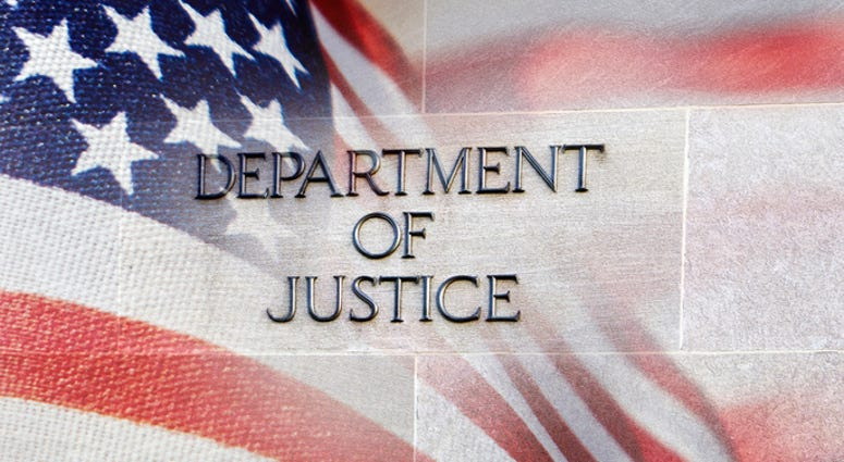 Department of Justice building sign with an American flag behind it