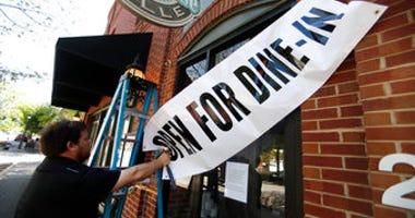 FILE - In this April 27, 2020, file photo, Jason Godbey hangs a banner over the entrance of Madison Chop House Grille as they prepare to shift from take out only to dine-in service in Madison, Ga. (AP Photo/John Bazemore, File)