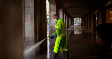 A worker disinfects the street to prevent the spread of COVID-19 in Barcelona, Spain, Thursday, March 19, 2020. For most people, the new coronavirus causes only mild or moderate symptoms.  (AP Photo/Emilio Morenatti)