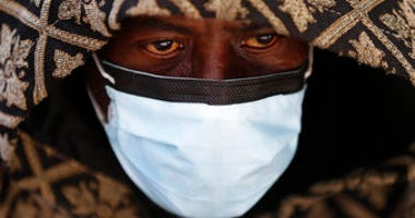 A man wears a protective mask while waiting for a bus in Detroit, Wednesday, April 8, 2020. (AP Photo/Paul Sancya)