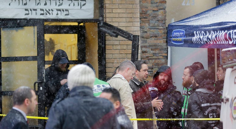 Jersey City's mayor Steven Fulop, center right, talks with first responders at the scene of a shooting in Jersey City, N.J., Dec. 11, 2019. Fulop says gunmen targeted a kosher market during a shooting that killed multiple people. (AP Photo/Seth Wenig)