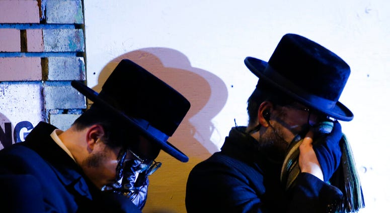 Orthodox Jewish men mourn during the funeral service of Mindel Ferencz who was killed in a kosher market that was the site of a gun battle in Jersey City, N.J., Wednesday, Dec. 11, 2019. (AP Photo/Eduardo Munoz Alvarez)