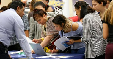 FILE - In this Sept. 18, 2019, file photo job applicants looks at jobs available at Florida International University during a job fair in Miami.  (AP Photo/Lynne Sladky, File)