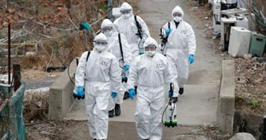 South Korean soldiers wearing protective gears walk to spray disinfectant as a precaution against the new coronavirus in Seoul, South Korea, Tuesday, March 3, 2020. (AP Photo/Lee Jin-man)