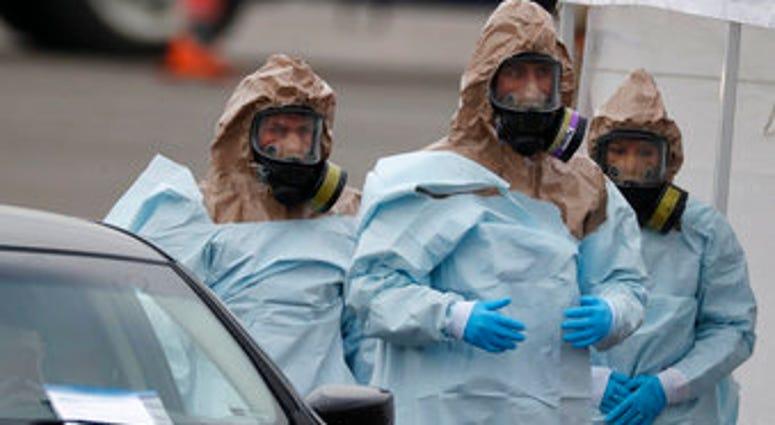 Colorado National Guard medical personnel prepare to perform coronavirus test on a motorist at a drive-thru testing site outside the Denver Coliseum Saturday, March 14, 2020, in Denver. (AP Photo/David Zalubowski)