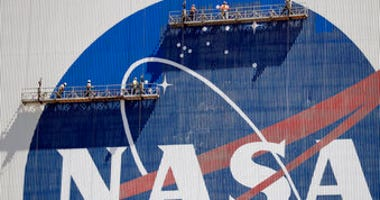 Workers near the top of the 526 ft. Vehicle Assembly Building at the Kennedy Space Center spruce up the NASA logo standing on scaffolds in Cape Canaveral, Fla., Wednesday, May 20, 2020. (AP Photo/John Raoux)