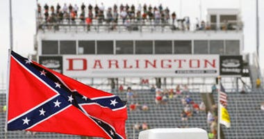 FILE - In this Sept. 5, 2015, file photo, a Confederate flag flies in the infield before a NASCAR Xfinity auto race at Darlington Raceway in Darlington, S.C. (AP Photo/Terry Renna, File)