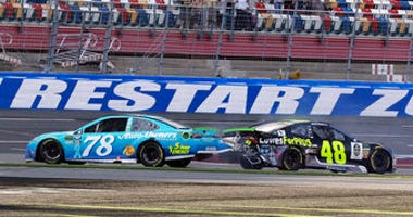 FILE - In this Sept. 30, 2018, file photo, Martin Truex Jr., (78) and Jimmie Johnson (48) crash on the final lap during the NASCAR Cup series auto race at Charlotte Motor Speedway in Concord, N.C.(AP Photo/Chuck Burton, File)