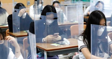 Senior students wait for class to begin with plastic boards placed on their desks at Jeonmin High School in Daejeon, South Korea, Wednesday, May 20, 2020. (Kim Jun-beom/Yonhap via AP)