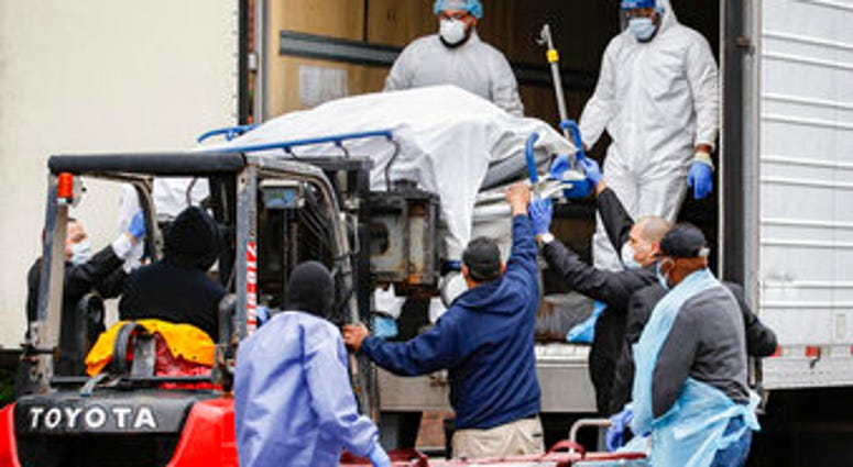 A body wrapped in plastic is unloaded from a refrigerated truck and handled by medical workers wearing personal protective equipment due to COVID-19 concerns. (AP Photo/John Minchillo)