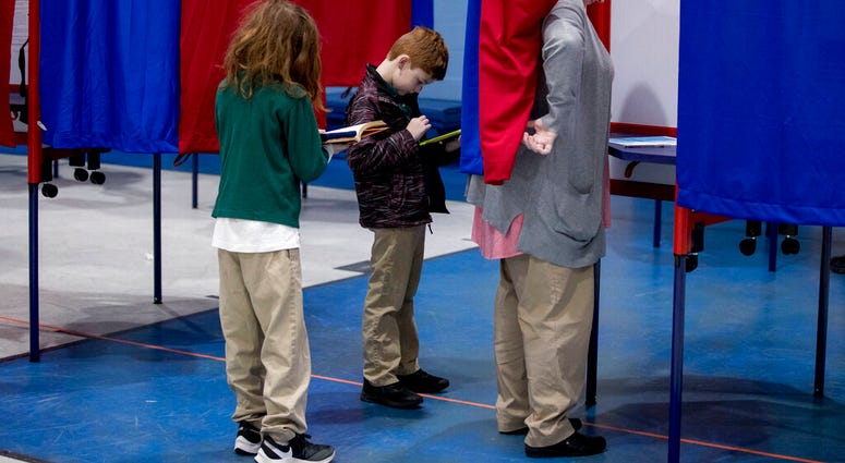 Samantha Murch accompanied by her two boys Alexander, 8, center, and Jacob, 11, left, votes in the New Hampshire primary at Bishop O'Neill Youth Center, Tuesday, Feb. 11, 2020, in Manchester, N.H. (AP Photo/Andrew Harnik)