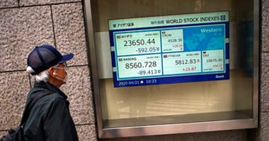 A man wearing a mask against the spread of the new coronavirus looks at an electronic stock board showing world stock indexes at a securities firm in Tokyo Tuesday, April 21, 2020.  (AP Photo/Eugene Hoshiko)