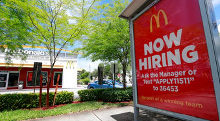 FILE - In this July 1, 2019, file photo, a help wanted sign appears on a bus stop in front of a McDonald's restaurant in Miami. (AP Photo/Wilfredo Lee, File)