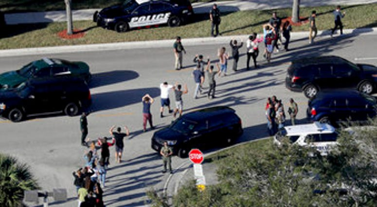 FILE - In this Wednesday, Feb. 14, 2018, file photo, students hold their hands in the air as they are evacuated by police from Marjory Stoneman Douglas High School in Parkland, Fla. (Mike Stocker/South Florida Sun-Sentinel via AP, File)