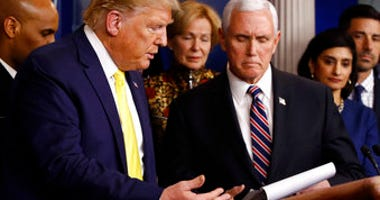 President Donald Trump gestures for Vice President Mike Pence to speak in the briefing room of the White House in Washington, Monday, March 9, 2020, about the coronavirus outbreak. (AP Photo/Patrick Semansky)