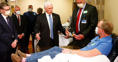 Vice President Mike Pence, center, visits Dennis Nelson, a patient who survived the coronavirus and was going to give blood, during a tour of the Mayo Clinic Tuesday, April 28, 2020. (AP Photo/Jim Mone)