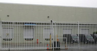 This Thursday, April 30, 2020 photo shows the gate outside a warehouse in Weston, Fla. used by the U.S. Drug Enforcement Agency. (AP Photo/Wilfredo Lee)