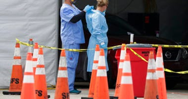 FILE - In this July 5, 2020, file photo, healthcare workers help each other with their personal protective equipment at a drive-thru coronavirus testing site outside Hard Rock Stadium in Miami Gardens, Fla. (AP Photo/Wilfredo Lee, File)