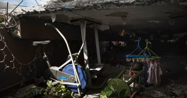 A stationary bike stands where the roof collapsed next to a home's game room located on the second floor, which is the top floor, after an earthquake hit Guanica, Puerto Rico. (AP Photo/Carlos Giusti)