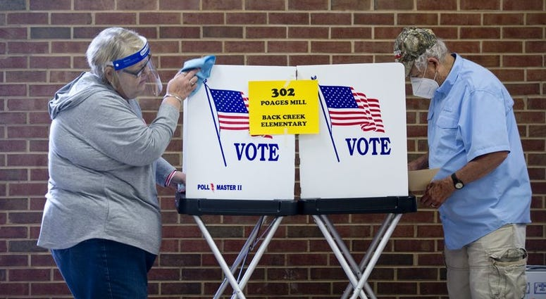 Glenda Patsel, left, wipes down a voting booth as Bobby J. Lambert fills out his ballot for the senate Republican candidates primary election, Tuesday, June 23, 2020, at Hidden Valley Middle School in Roanoke, Va.