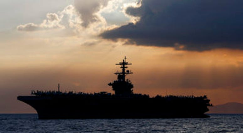 FILE - In this April 13, 2018, file photo the USS Theodore Roosevelt aircraft carrier is anchored off Manila Bay west of Manila, Philippines. (AP Photo/Bullit Marquez, File)