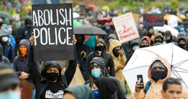 "A protester holds a sign that reads ""Abolish Police"" during a ""Silent March"" against racial inequality and police brutality that was organized by Black Lives Matter Seattle-King County, Friday, June 12, 2020, in Seattle. (AP Photo/Ted S. Warren)"