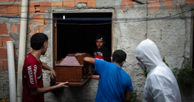 Relatives help a SOS Funeral worker, wearing protection equipment amid the new coronavirus outbreak, remove the body of Eldon Cascais from his home in Manaus, Brazil, Saturday, May 9, 2020. (AP Photo/Felipe Dana)