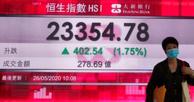 A woman wearing face mask walks past a bank electronic board showing the Hong Kong share index at Hong Kong Stock Exchange Tuesday, May 26, 2020. (AP Photo/Vincent Yu)