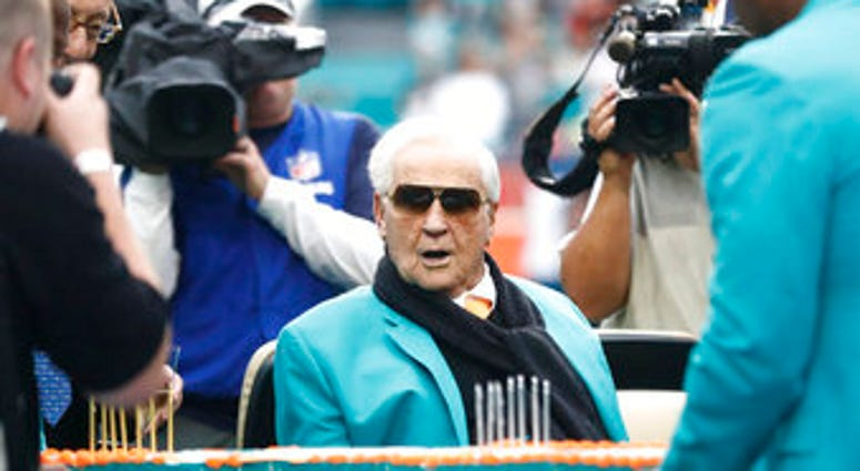 FILE - Former Miami Dolphins head coach Don Shula looks at a large cake celebrating the 1972 undefeated season and his birthday during half time at an NFL football game against the Cincinnati Bengals. (AP Photo/Brynn Anderson, File)
