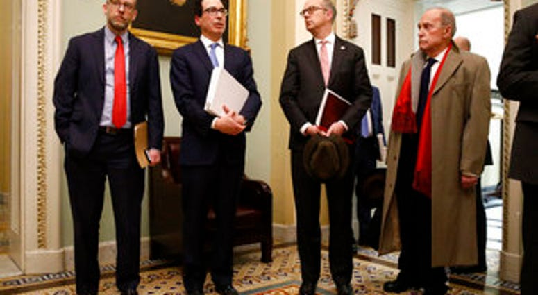 Treasury Secretary Steve Mnuchin, second from left, speaks with members of the media as he departs a meeting with Senate Republicans on an economic lifeline for Americans affected by the coronavirus outbreak. (AP Photo/Patrick Semansky)