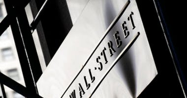 FILE - This July 15, 2013, file photo, shows a sign for Wall Street outside the New York Stock Exchange. (AP Photo/Mark Lennihan, File)