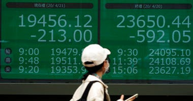 A woman wearing a mask against the spread of the new coronavirus walks past an electronic stock board showing Japan's Nikkei 225 and New York Dow index at a securities firm in Tokyo Tuesday, April 21, 2020. (AP Photo/Eugene Hoshiko)