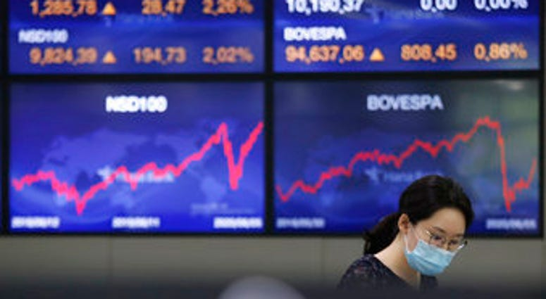 A currency trader watches monitors at the foreign exchange dealing room of the KEB Hana Bank headquarters in Seoul, South Korea, Monday, June 8, 2020. (AP Photo/Ahn Young-joon)