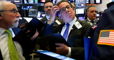 Sal Suarino, center, works with fellow traders on the floor of the New York Stock Exchange, Tuesday, March 10, 2020. (AP Photo/Richard Drew)
