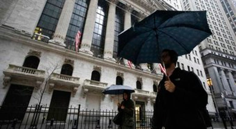 People walk in the rain as they pass the the New York Stock Exchange, Friday, March 13, 2020. (AP Photo/Mark Lennihan)