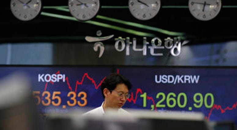 A currency trader walks by screens showing the Korea Composite Stock Price Index (KOSPI), left, and the foreign exchange rate between U.S. dollar and South Korean won at the foreign exchange dealing room in Seoul, South Korea. (AP Photo/Lee Jin-man)